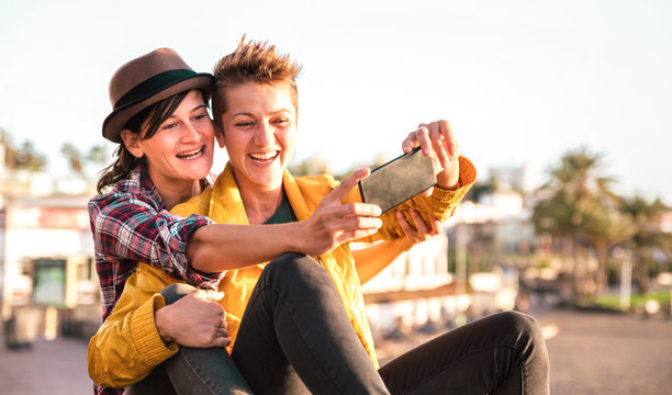 Female friendship concept with girls couple taking selfie outdoors in Tenerife - Lgbtq genuine love relationship with happy millennial girlfriends having fun - Happy playful women on warm filter