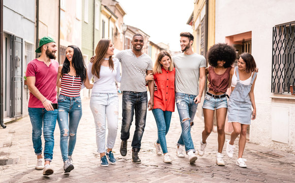 Multiracial millennial friends walking in city center - Happy guys and girls having fun around old town streets - University students on travel vacations  - Warm desaturated filter