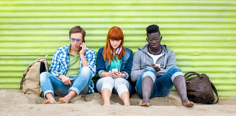 Multiracial friends using mobile smart phone at beach on relax moment - Young bored people addicted by smartphone - Technology concept with always connected millennials - Vivid green filter