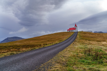 Path to faith: Against the odds and adversity of the weather, the winding road leads the path to faith under ominous cloud -- Iceland