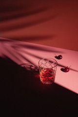 Red Cherry Cocktail with Fresh Cherries on Pink Background with Plant Shadows