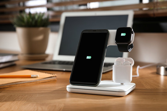 Mobile phone, earphones and smartwatch charging with wireless pad on wooden desk. Modern workplace device