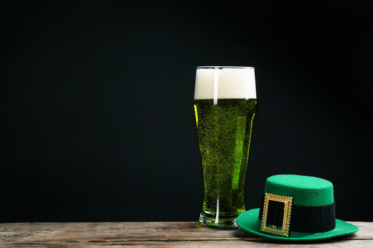 Green beer and hat on wooden table against black background, space for text. St. Patrick's Day celebration