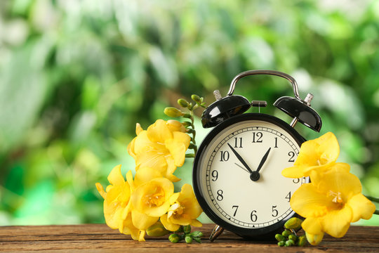Alarm clock and beautiful spring flowers on wooden table. Time change concept
