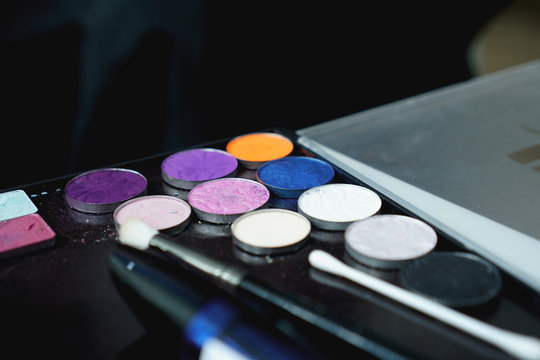 Use palette of shadows for makeup on a blurred background, closeup