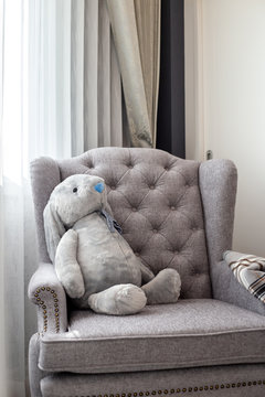 A gray rabbit doll lying on a gray sofa in a children's bedroom