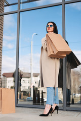 Foto op Canvas Marokko girl with brunette hair wearing sunglasses and holding shopping eco bags