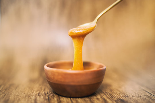 Manuka honey spoon dipped in golden liquid natural superfood on wooden background.