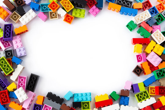 Close-up of a cluttered pile of colorful Lego bricks viewed from above with place for content or text in the middle. Isolated on white background, top view. Copy space.