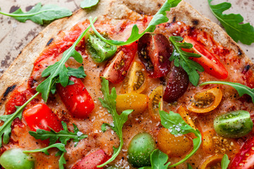 Directly above view of pizza with cherry tomatoes and arugula