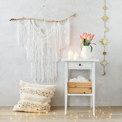 Spring boho home interior decor: macrame wall hanging decoration, white bedside table, vase, pink tulips flowers, lighted candles, pillow, led garland glowing lights. Light cozy modern stylish room.