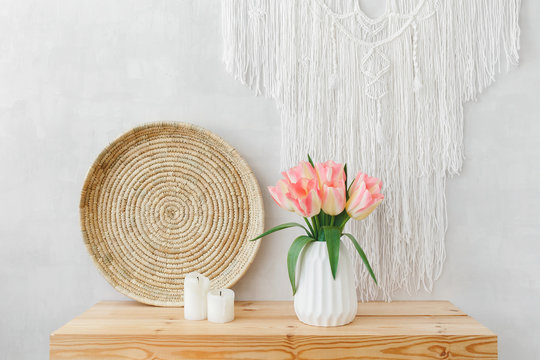 White ceramic vase, bouquet of pink tulips flowers, wicker tray, candles, macrame wall hanging decoration on a wooden table or shelf on a background of light gray wall. Spring boho home interior decor