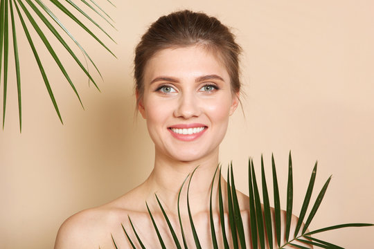 Portrait of a beautiful young girl with nude makeup and palm branches on a colored background. The concept of healthy and clean skin, skin care.