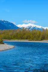 Fototapete - Majestic mountain river in winter over snow mountains and blue sky in Vancouver, Canada.