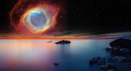 Wall Mural - Long exposure image of dramatic sky and seascape with rock and stellar explosion of Supernova
