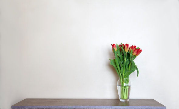 Glass vase of red tulips on a grey wooden shelf, beige background, minimalism interior decor, copy space