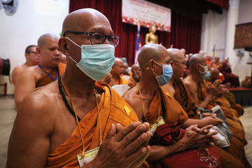 Buddhist monks wearing protective face masks pray during a blessing ceremony for the people affected by the COVID-19 coronavirus outbreak, at a temple in Kuala Lumpur