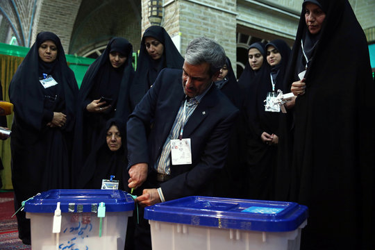 A poll worker opens a ballot box after the parliamentary election voting time ended in Tehran