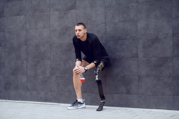 Fotomurales - Full length of handsome caucasian sportsman with artificial leg leaning on wall, holding refreshment and resting from running.