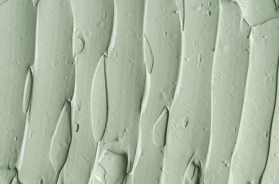 Gray bentonite facial clay (mask, face cream, body wrap) texture close up, selective focus. Abstract background with brush strokes.