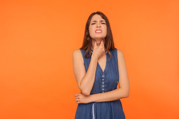Unhealthy brunette woman in dress touching neck and grimacing in pain, suffering sore throat, respiratory infection with larynx inflammation, flu. indoor studio shot isolated on orange background