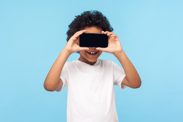Positive lovely happy little boy with curly hair covering eyes with cellphone and smiling, unknown child hiding face with mobile phone, anonymous user. indoor studio shot isolated on blue background