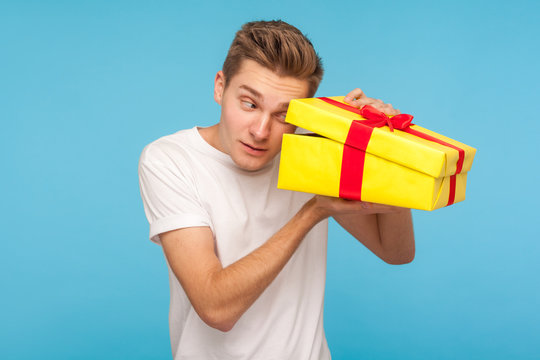 Nosy impatient man in white t-shirt looking inside gift box with curious happy expression, opening present before celebration, peeking with interest. indoor studio shot isolated on blue background