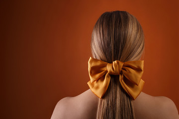 blond female hairstyle with color ribbon on orange wall background with copyspace. close up of blonde girl head with carroty bow in her hair, rear view. fashion style photoshoot of woman in studio
