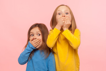 Portrait of two little frightened girls covering mouth with hands and looking with scared eyes, children afraid to speak, taboo topic, intimidation. indoor studio shot isolated on pink background