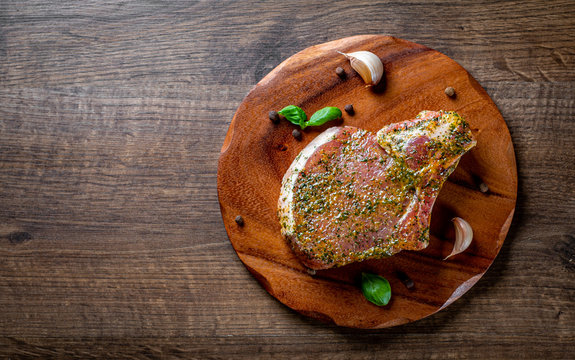 Raw Pork Loin chops marinated meat Steak for bbq on wooden table background
