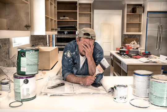 Exhausted, tired painter, face in hands holding wet paint brush in messy home kitchen fixer upper remodel, dripping paint cans, PREVIOUSLY SUBMITTED & ACCEPTED, TOP SELLER
