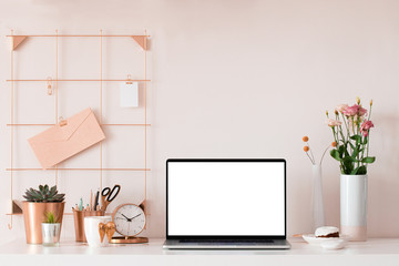 Laptop with blank white screen on office desk interior. Stylish rose gold workplace mockup table view.