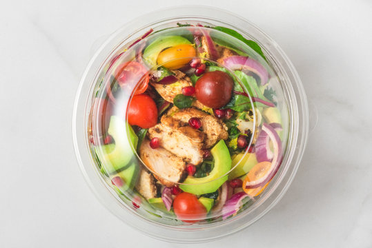 Plastic package with healthy chicken salad with avocado , tomatoes and pomegranate to take away