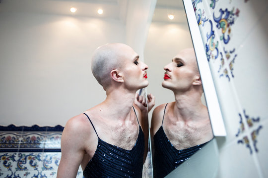 Handsome man doing makeup in front of a mirror
