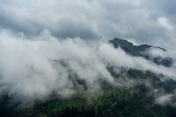 Misty Clouds moving in front of a bavarian mountain peak