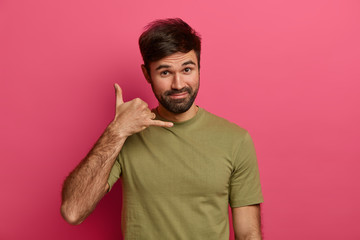 Handsome bearded man makes phone gesture near, asks girlfriend telephone number, says so call me maybe, has satisfied expression, dressed casually, poses against pink background. Body language Wall mural