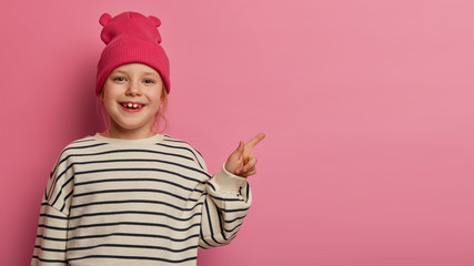 Adorable preschooler feels happy while points at upper right corner, demonstrates something interesting, attracts your attention to discounts in toy shop, wears rosy hat and striped sweater. Wall mural