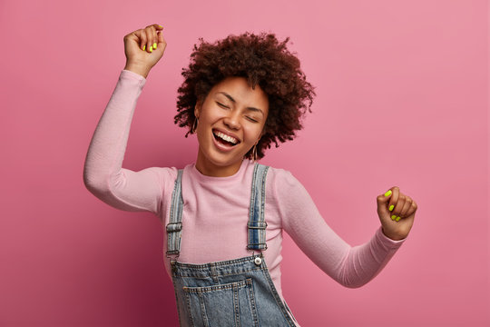 Happy dark skinned girl enjoys every moment of life, dances and moves, raises arms and clenches fists, closes eyes, has good mood, wears denim sarafan and turtleneck, isolated on pink background
