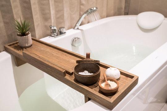 Modern and comfortable bathroom, Bath tub with wooden table and toiletries, Salt, Herb, Bath Bomb.