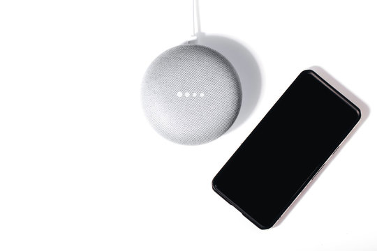 Digital Assistant concept. Flat lay of smart speaker with LED lights activated and smartphone isolated on white background.