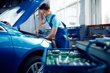 Worker in uniform checks engine, car service