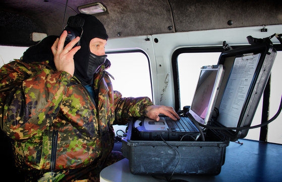 A man in a military uniform, wearing a mask on his face listens to radio conversations