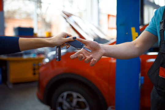Female driver gives keys to worker in uniform