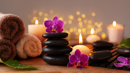 Spa, beauty treatment and wellness background with massage stone, orchid flowers, towels and burning candles.
