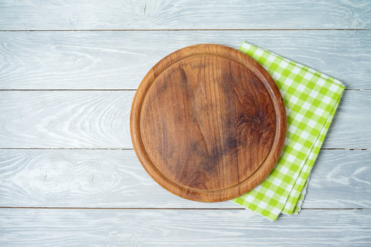 Round pizza board with green checked tablecloth on rustic wooden table .Kitchen, cooking or baking mock up background for design.