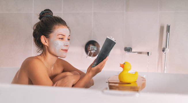 Asian girl running a bath at home taking relaxing time for herself in cozy winter apartment applying clay mask and reading a book soaking in hot water with rubber duck toy on bathtub caddy.