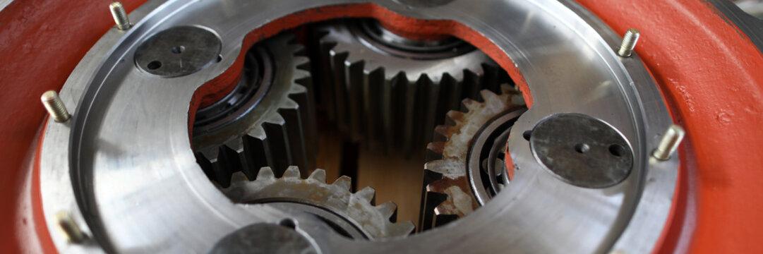 Big mechanical gear part with set of cogwheels inside close-up