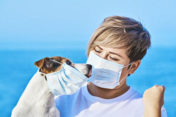 Woman in protective face mask looking at dog wearing medical mask