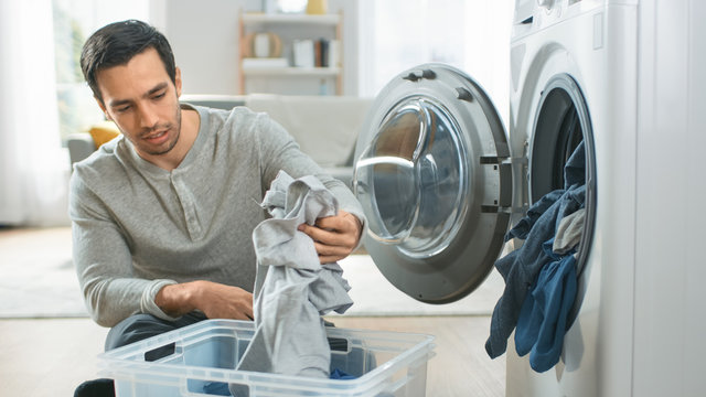 Handsome Smiling Young Man in Grey Jeans and Jumper Sits in Front of a Washing Machine at Home. He Loads the Washer with Dirty Laundry. Bright and Spacious Living Room with Modern Interior.