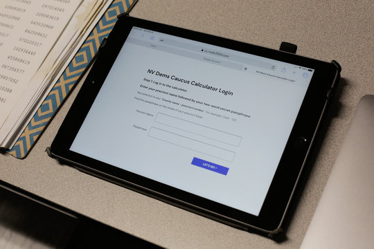 A login page is displayed on an iPad at a Nevada Caucus voting site at Coronado High School in Henderson